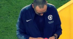 Sarri looking at his gold medal after winning the Europa League with Chelsea