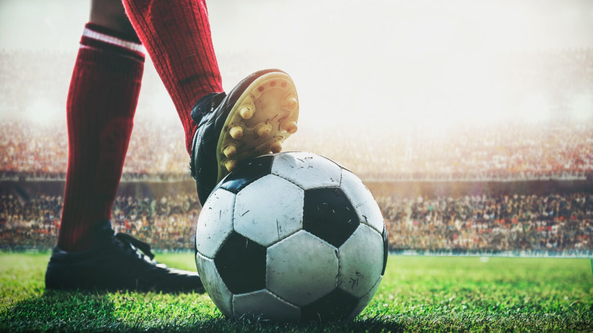 feet of soccer player tread on soccer ball for kick-off in the stadium