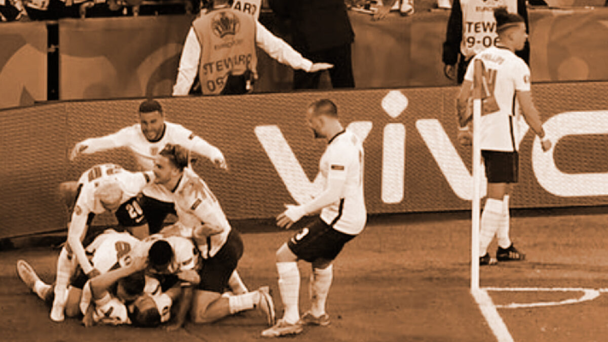 England players pile on Harry Kane to celebrate his extra time penalty against Denmark