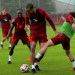 Joel Matip shoves Takumi Minamino out of his way before going on a run in training