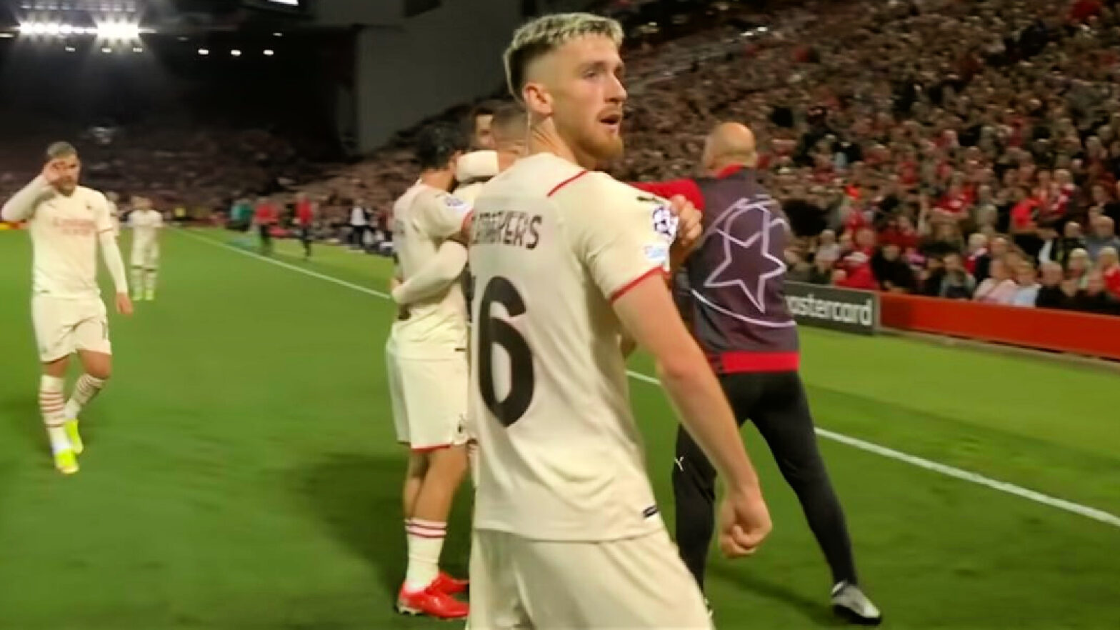 Alexis Saelemaekers points at the UCL badge against Liverpool